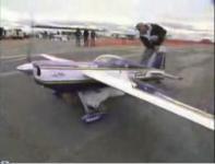 ラジコン飛行機の下に張り付いて空を飛ぶ男