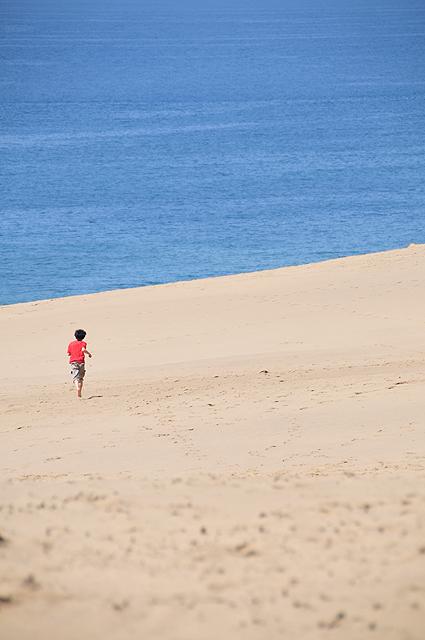 砂丘を走る少年