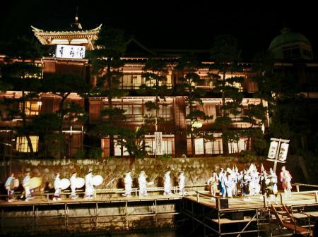 川の上の舞台で阿波踊りを披露