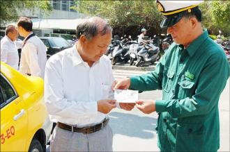 花蓮郵局郵務稽#26597;鄭夏俊(右),把日本遊客寄來的明信片送到曾傳富(左)手中