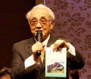 創立40周年記念特集の歌集を手に挨拶する蔡焜燦・現代表