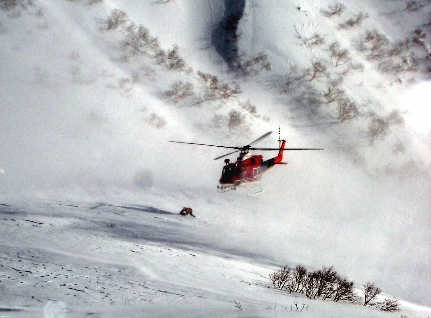強風下、雪面へ近づくヘリ②から飛び降りる救助隊員★