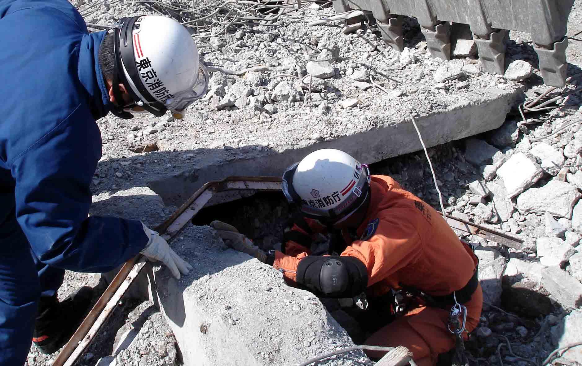 瓦礫の中に消防の人が隠れる
