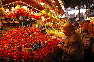 市場でイチゴを見つめるスペインおじさんの画像