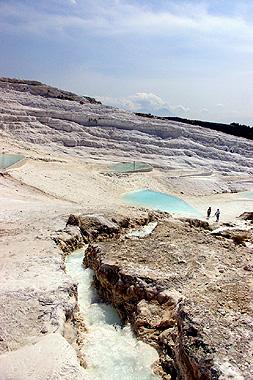 パムッカレの石灰棚の画像。雪のような岩に、ビビットな水色の温泉水が巨大な水たまりを作っている
