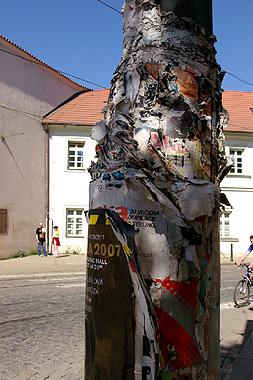 電柱にポスターが何重にも重ね貼りされてブ厚くなっている画像