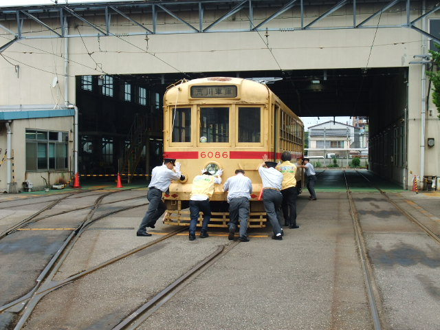 職員に押されて移動する電車